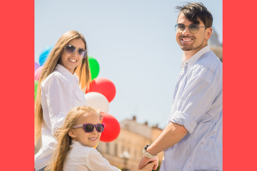 Happy young family with bunch of balloons having fun outdoors on sunny day.