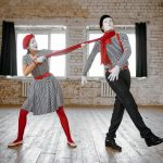 Male and female mime artists, strangulation with a scarf parody scene, comedy. Pantomime theater, comedian, positive emotion, humour performance, funny face mimic and grimace